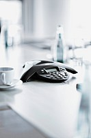 Coffee cup, telephone and documents on desk