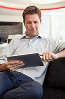Smiling businessman in office using digital tablet