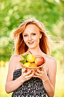 Portrait of young pretty blonde smiling woman wearing black top, holding basket with fruits at summer green park.