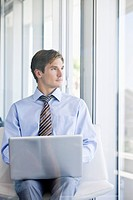 Businessman with laptop on laps looking through window (thumbnail)