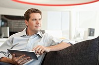 Businessman with digital tablet looking away