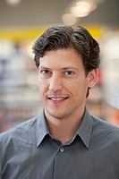 Portrait of smiling mid adult man in supermarket