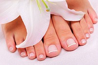 Beautiful well_groomed female feet with the French pedicure and flower