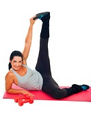 Cheerful healthy woman stretching leg and sittingon red mat against white background