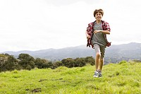 Pre_ teenage Boy on Top of a Mountain Running in the Grass towards Camera