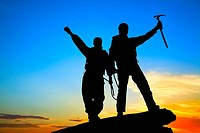 Two silhouettes of climbers on the mountain top