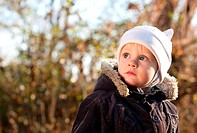 Cute child looks upward directed against the background blurred nature