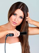 Portrait of beautiful woman, she using hair straighteners