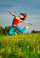 Happy young woman in sport wear jumping on a sunset field