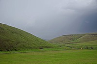 Green arid hills below dark storm clouds