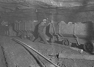Boy braking on motor train 10 hrs. a day. Where mining, loading, etc. is done by machinery. Live wire above is sometimes not higher than a man´s head.