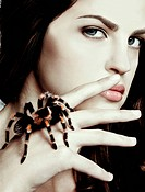 close_up portrait of girl with brachypelma smithi spider creeping over her hand