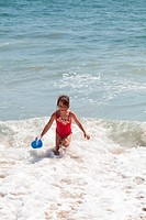 Very excited little girl running in the ocean surf with a blue bucket
