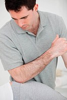 Physiotherapist using his elbow on the hip of a woman in a room