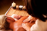 Masseur doing massaging backbone of woman in spa salon