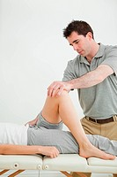 Serious physiotherapist stretching a leg while standing in a room