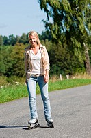 Inline skating young woman wearing jeans on sunny asphalt road