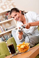 Students _ Female teenager playing video game holding game pad in living room
