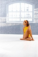 Portrait of ethnic dancer girl sitting on floor of exercise room, concentrating on training, copyspace.
