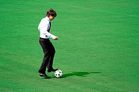 Man in suit playing in football on the stadium