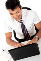 Young Nepalese businessman in office at desk in front of a laptop. Studio shot. White background