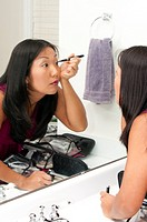 A beautiful young asian woman applying makeup