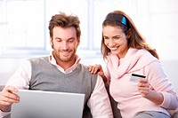 Happy young couple shopping online, using laptop and credit card, smiling.