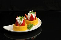 strawberry shortcake on a white plate isolated on a black background