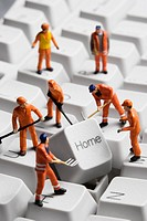 Worker figurines posed around the Home key on a computer keyboard.