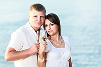 Young couple with glasses of champagne near the ocean