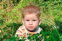 Little blond boy sitting on a green meadow