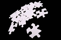 white puzzle pieces scattered on black background