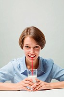smiling girl with a milkshake at the table
