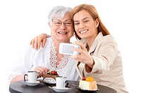 Senior mother and young daughter sitting at coffee table, photographing themselves by digital camera, smiling happily.