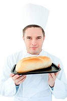 Charismatic male cook holding a bread into the camera against white background
