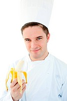 Charming male cook holding banana smiling at the camera against white background
