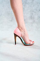 Smooth female legs on a grey background in pink shoes