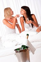 Two young women having fun with champagne in luxury hotel room