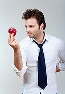 man in white shirt and tie holding red apple looking - isolated on gray