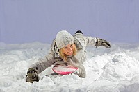 Pretty blonde on snowboard swim freestyle in snow on dark blue background.