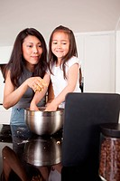 Mother and daughter baking cookies, following a receipe on a digital tablet