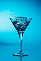Vermouth cocktail inside martini glass over blue background