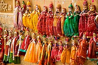 multicolored puppets hanged up to a wall in Jaisalmer, rajasthan