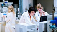 female researchers/chemistry students doing research in a chemistry lab color toned image, shallow DOF