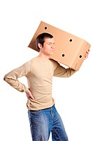 A young man suffering from back pain while lifting a large box isolated on white background