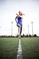 A beautiful caucasian woman exercises in a sport field