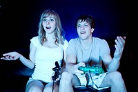A shot of a young couple playing video games in the living room