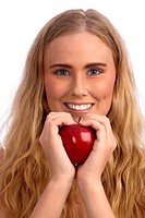 Beautiful blond caucasian young woman smiling and holding a red apple, creating a heart with her hands