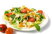 healthy fresh garden salad on a plate, isolated on white, tomatoes in foreground