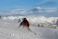 Skier is carving on a slope with daylight moon on horizon